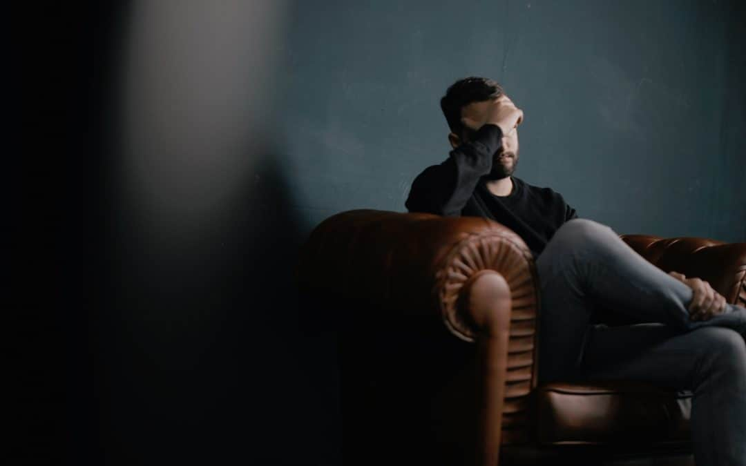 Picture of a man sitting down while covering his eyes with his hand.